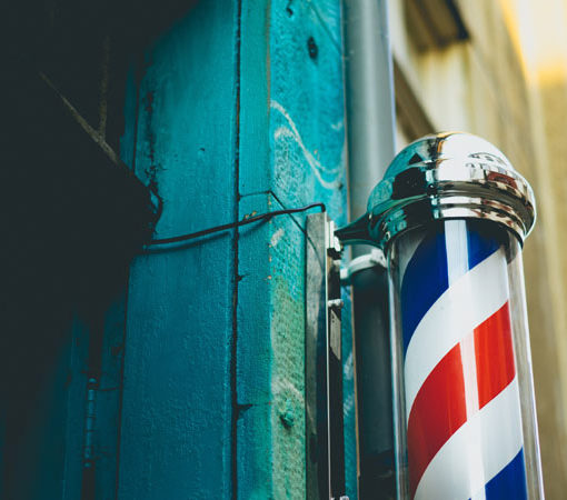 a striped barber pole in front of a green doorway