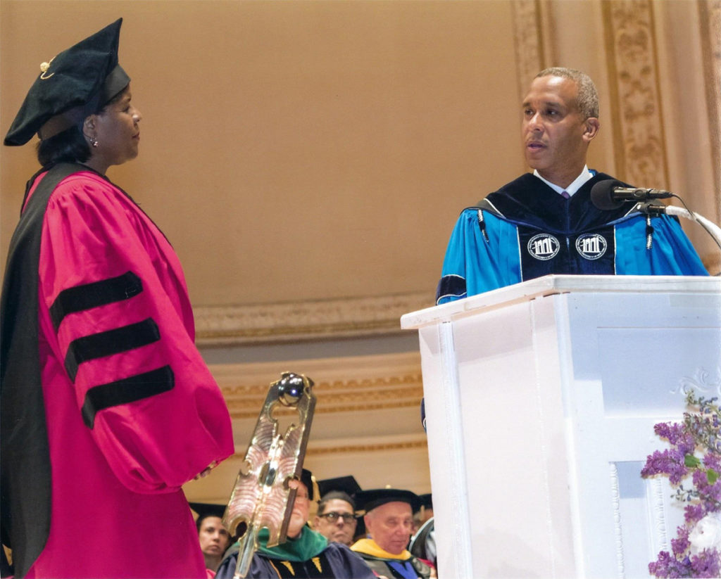 A black woman in a pink doctoral cap and gown approaches a man in a blue robe during a commencement ceremony