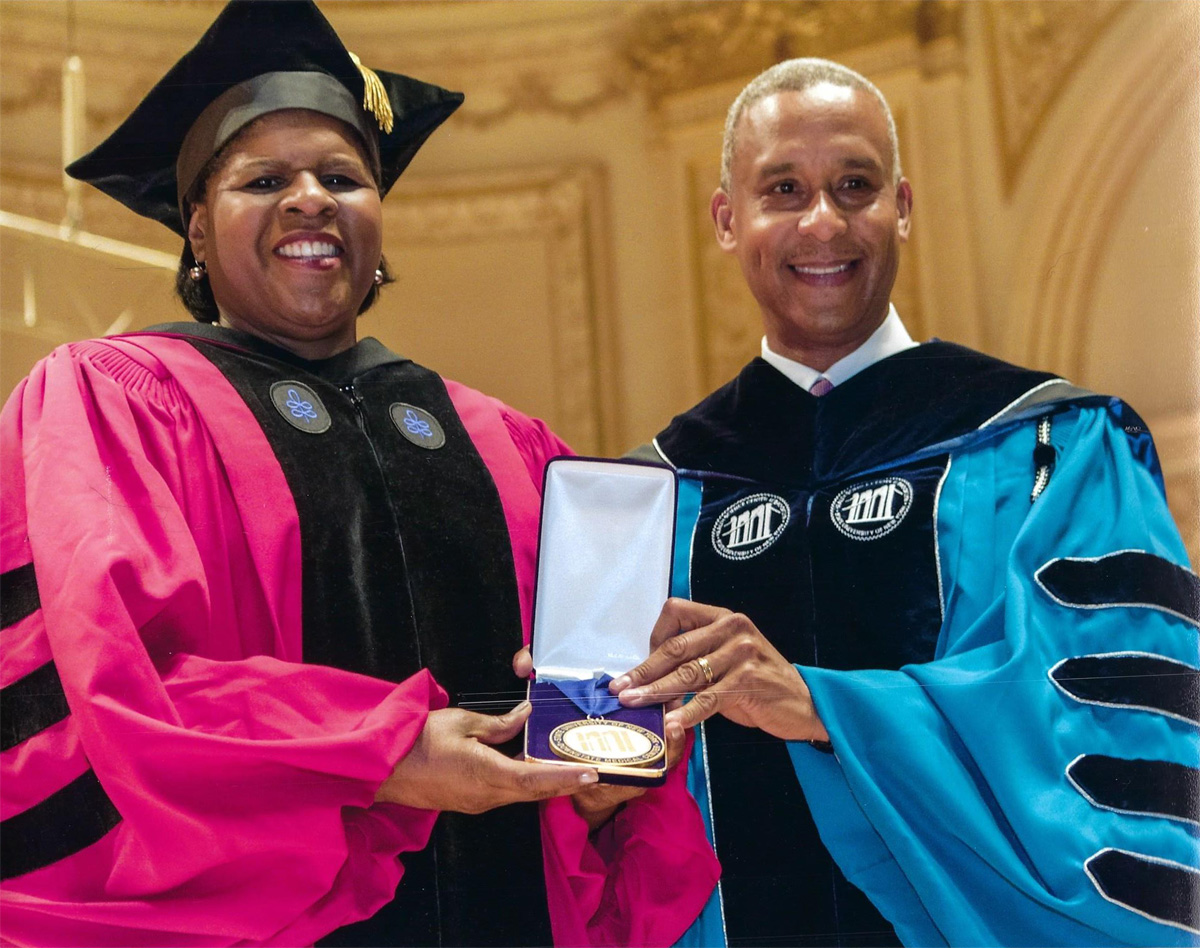 a man and a woman in doctoral robes pose with an award.